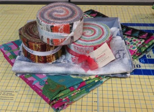 Three jelly rolls placed on top of two jelly roll race quilts that have been folded up.