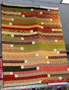 Photo of Jelly Roll Race quilt with white squares sewn in between each strip
