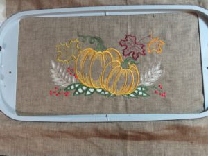 Photo of hooped linen for cutwork tea towel with finished embroidery