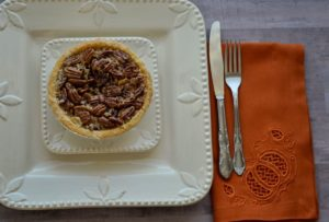Photo of plate with rust-colored napkin with cutwork pumpkin from Dinner Party designs by Kimberbell, highlighted in October Sew Fun