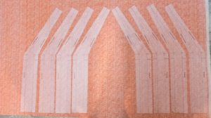 "Photo of interfacing for pattern pieces ""2A"" and ""2AR"" ironed on to the orange fabric for the square tuffet"