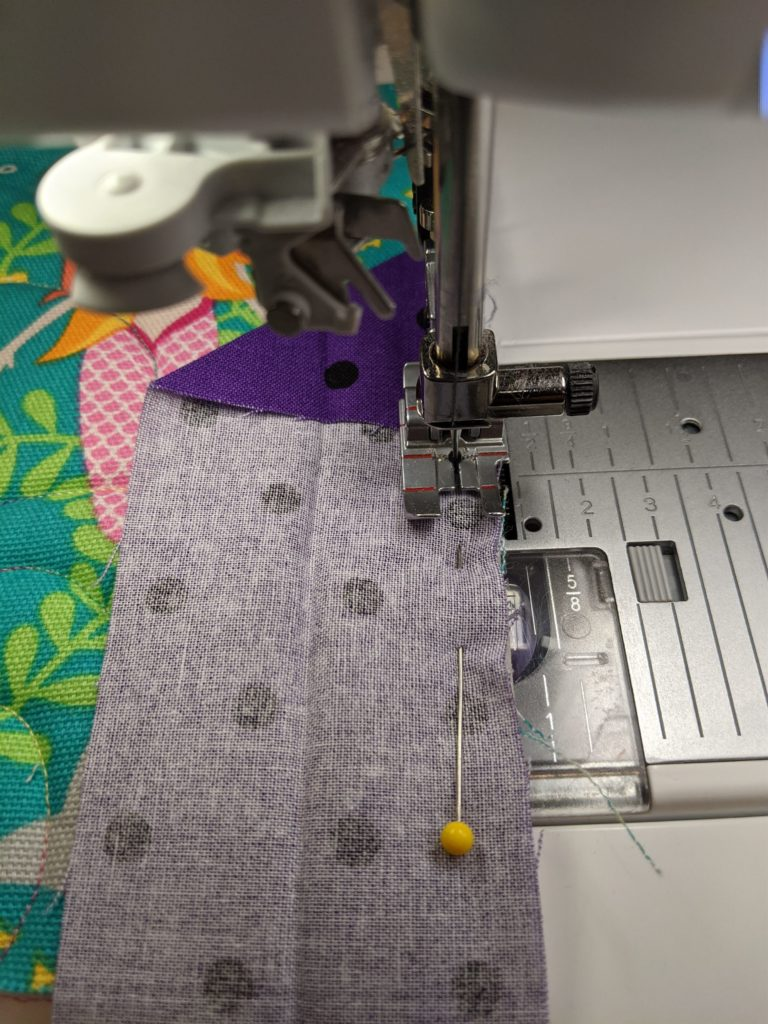 Photo of sewing down raw edge of binding to raw edge of quilt